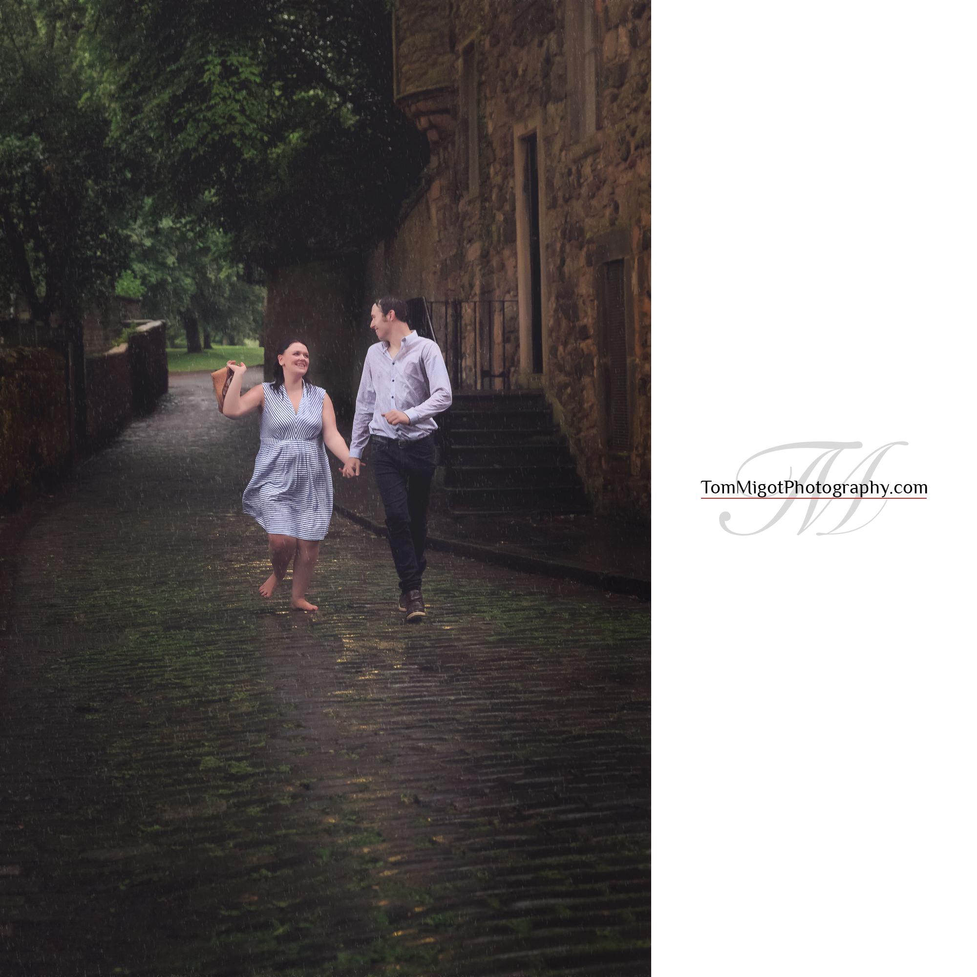Les futures mariés dans une rue d'Edimbourg sous la pluie pendant leur séance photo d'avant mariage