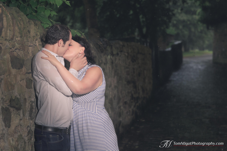 Les futures mariés s'embrassent dans une rue d'Edimbourg sous la pluie pendant leur séance photo d'avant mariage