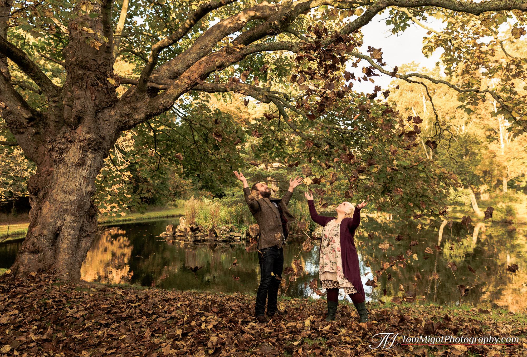 Les futurs mariés jouant avec les feuilles morte pendant la séance photo d'avant mariage