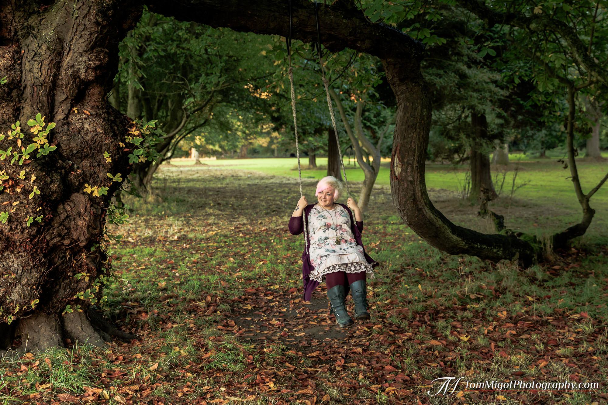 La future mariée sur une balançoire dans les bois pendant la séance photo d'avant mariage
