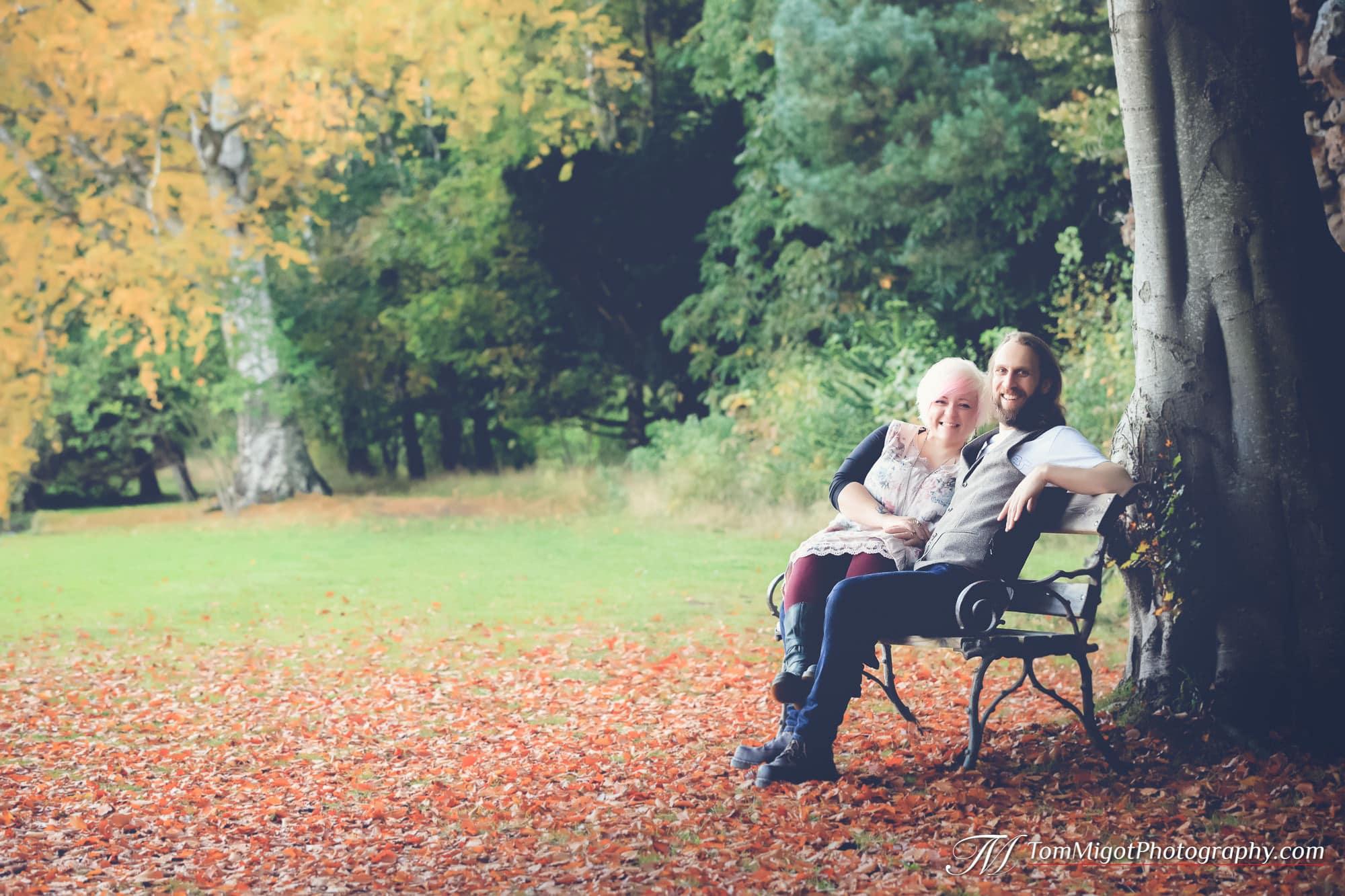Les futurs mariés sur un bancs dans les bois pendant la séance photo d'avant mariage