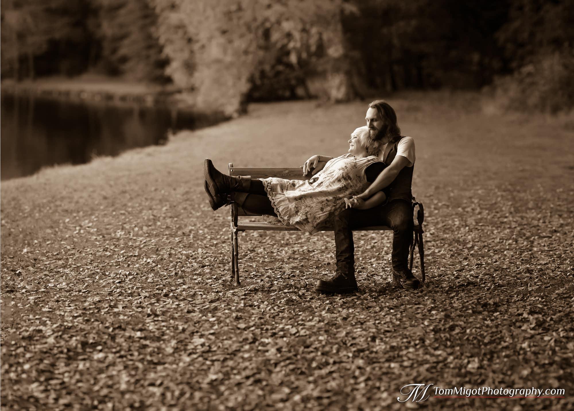 Moment intime pour les futurs mariés sur un bancs dans les bois pendant la séance photo d'avant mariage
