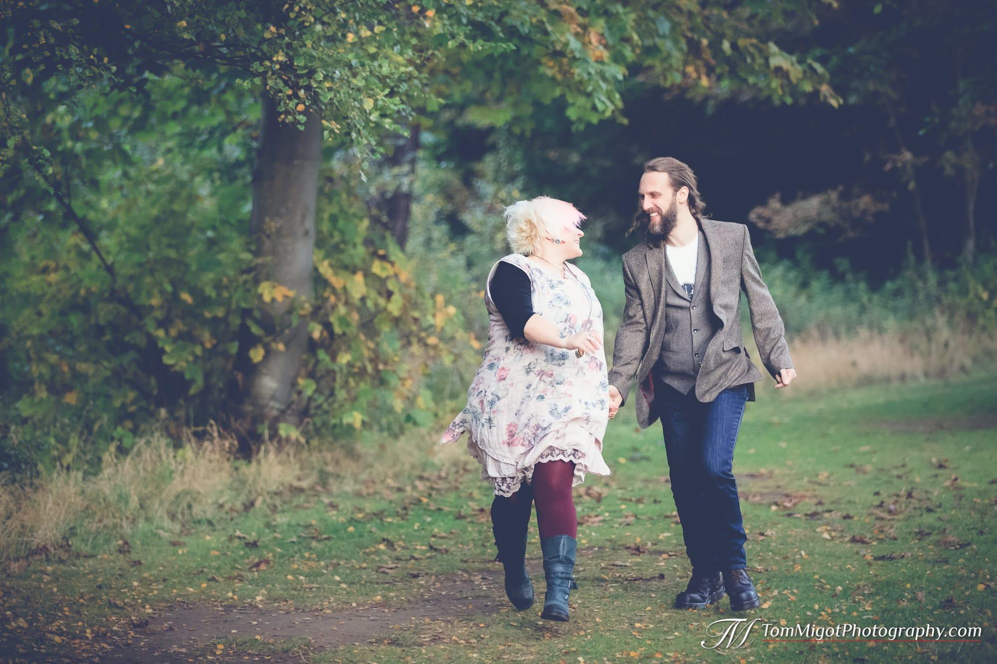 Les futurs mariés qui s'amusent dans les bois pendant la séance photo d'avant mariage