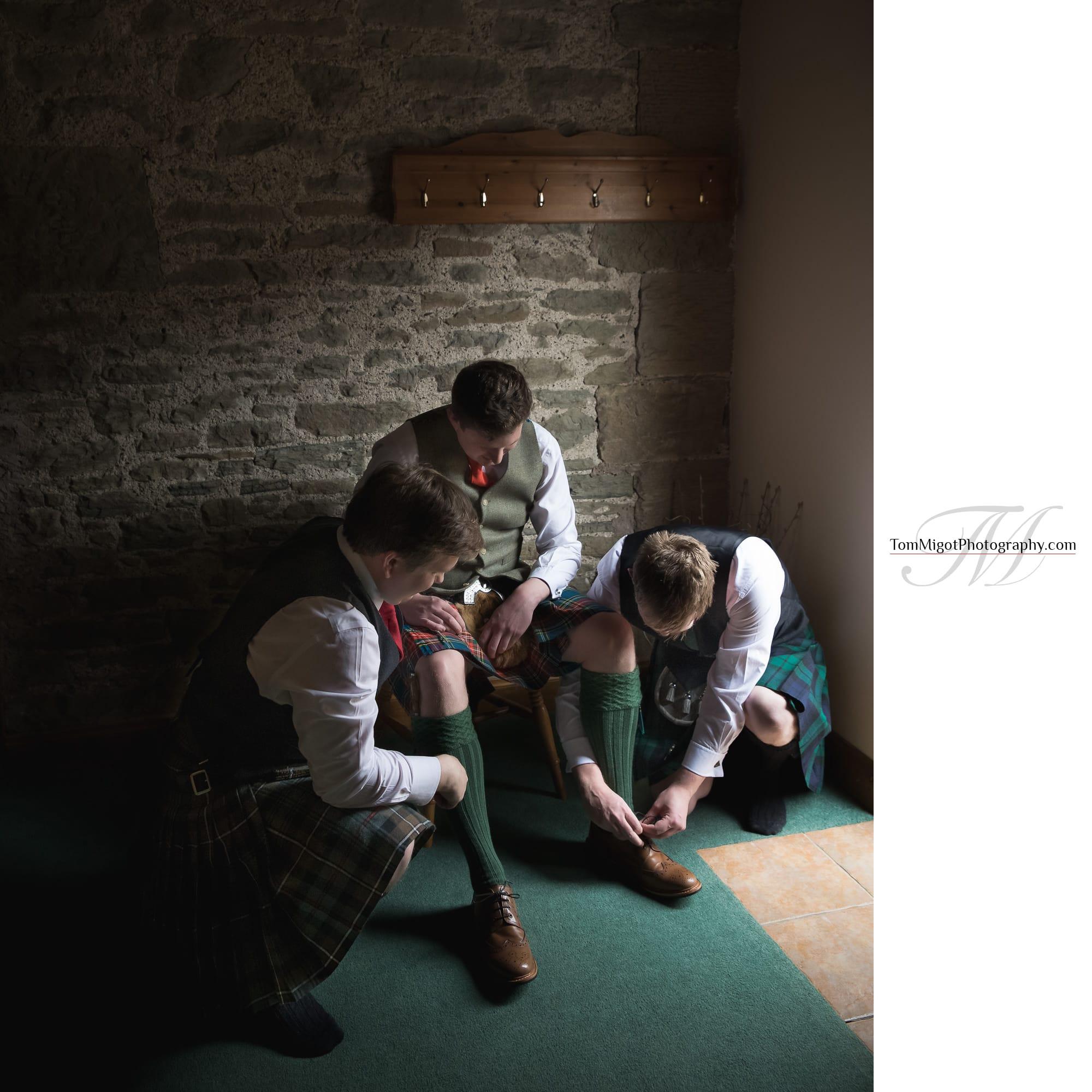 Les garçons d'honneur aident le marié avec ses chaussures