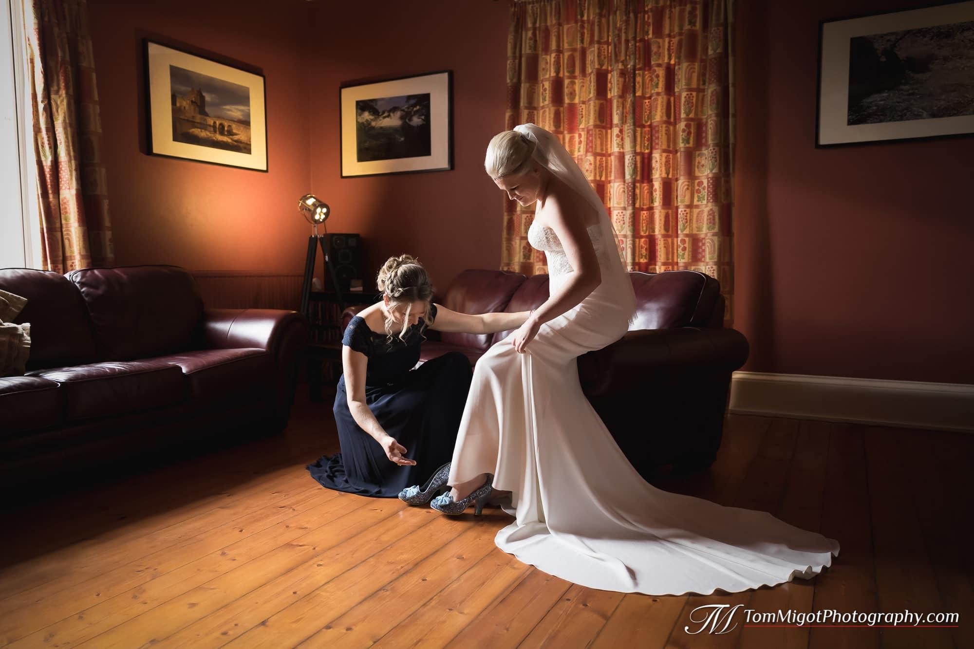 Une demoiselle d'honneur aide la mariée avec ses souliers