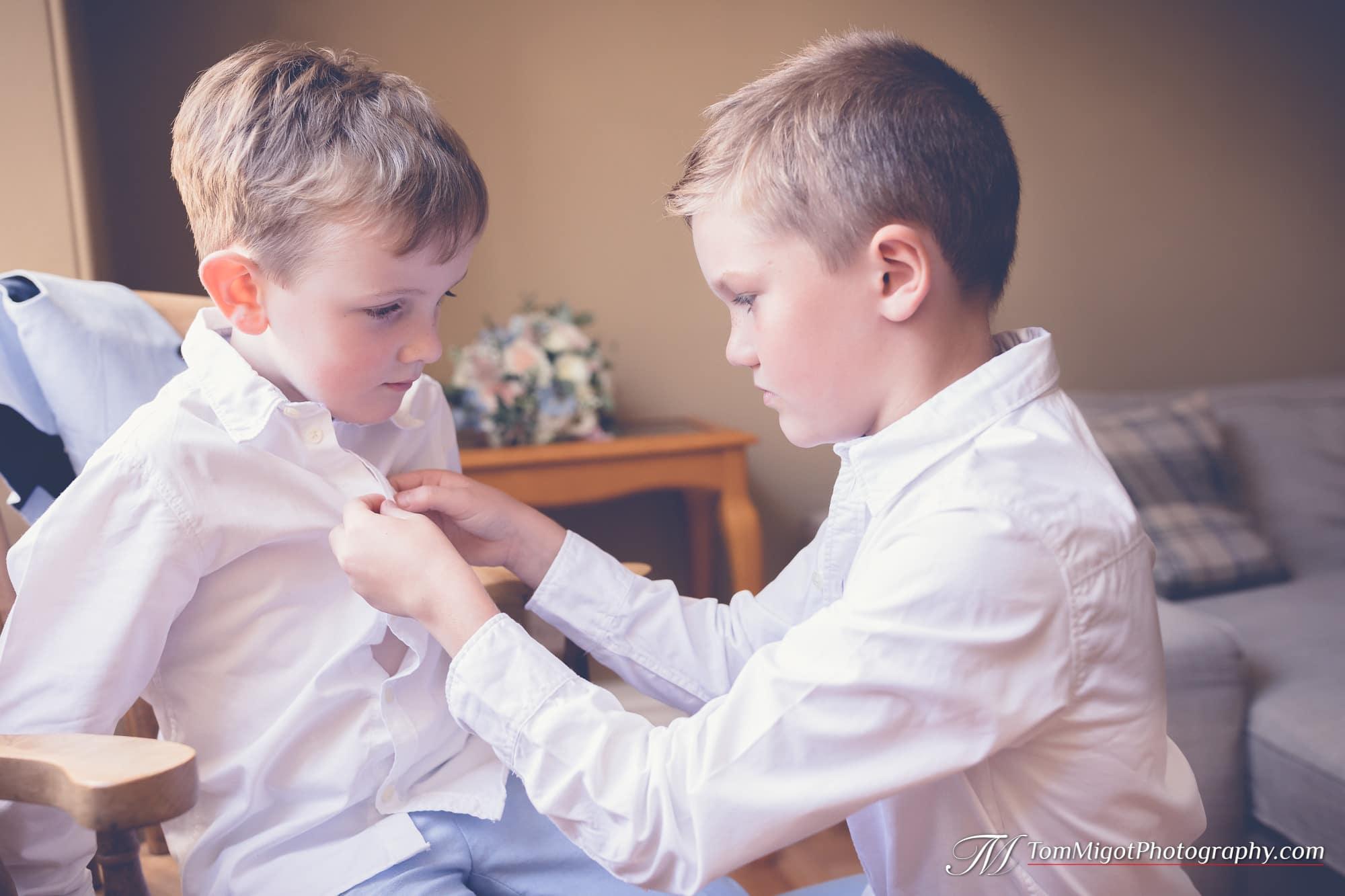 Le grand cousin aide à boutonner la chemise du plus petit
