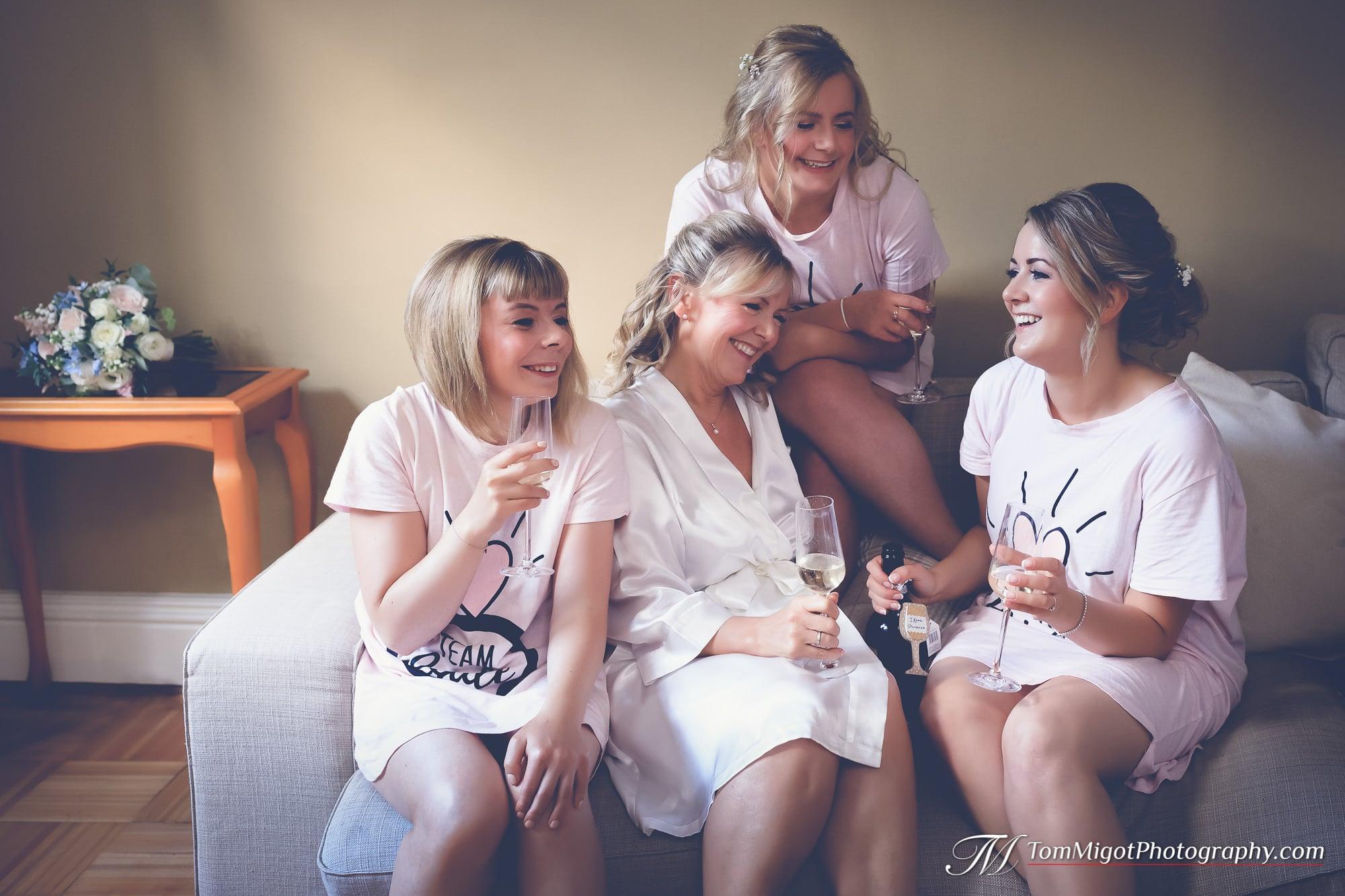 La mariée partage une bouteille de prosecco avec ses filles